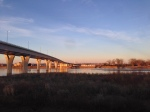 The golden hour lights up the Mandan side of the river and the pillars supporting the memorial bridge.